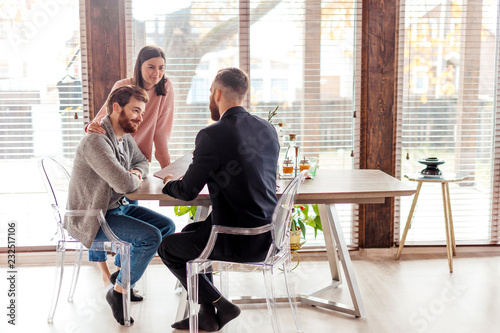 Fototapeta Young caucasian couple consulting with bank financial adviser before buying new house. Two bearded men sitting at table and checking documents while woman stands behind. obraz