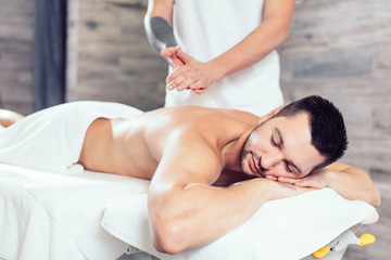 Fototapeta masseur preparing his hands for massage while his clent li lying with closed eyes. close up side view photo