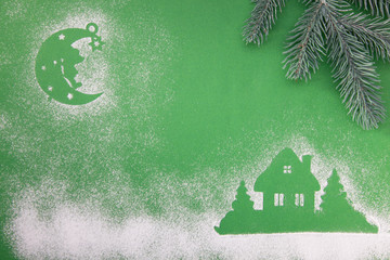 Christmas toys, handmade wooden moon star and home, on a green background.