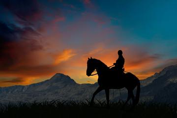 Sylwetka jeździec jedzie na koniu przy zmierzchem górami