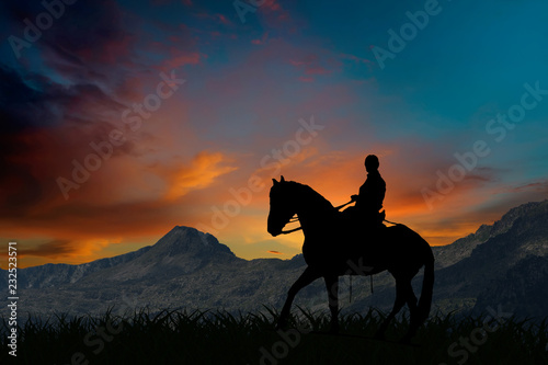 Silhouette of a horseman riding on horseback at sunset by mountains Slika na platnu
