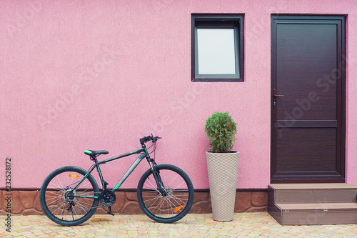 Deurstickers Fiets bike near the wall with a doorway and a window, part of the pavement