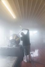 Man Washing Machine Using Steam From Power Hose