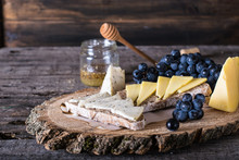 Assorted Cheeses With Grapes, Bread, Honey On Dark Wood Background. Goat Cheese With Herbs. Natural Wooden Board. Italian Appetizer. Bruschetta With Cheese. Still Life Of Food. Breakfast Concept.