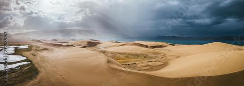 storm clouds above sand dunes beside a lake, khar nuur lake, mongolia