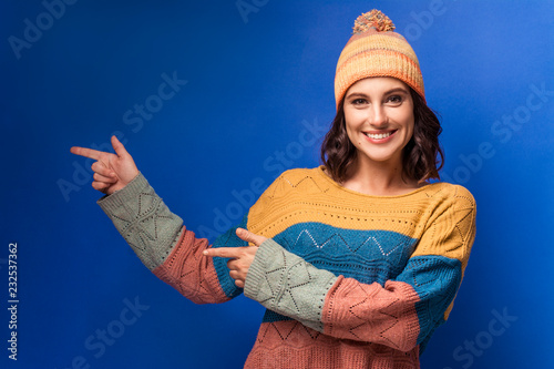 Fototapeta smiling girl in knitted sweater and yellow hat  obraz