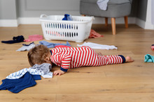 Baby Lying On Floor In Laundry Mess