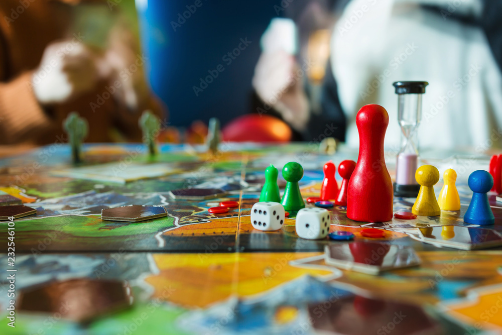 Fototapeta Board game concept- board game field, many figures, meeple, dice, coins and sandglass. Two people play holding cards on blurred background