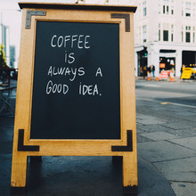 Quote About Coffee On A Board Along The Street