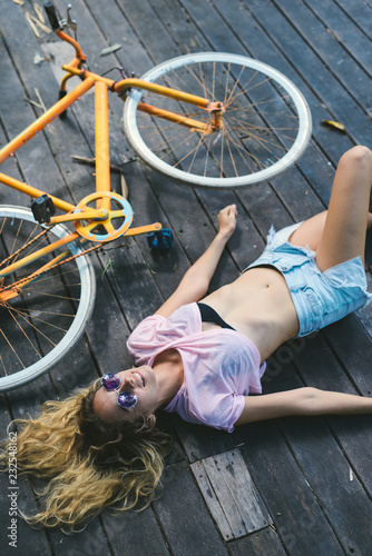 Young girl resting on the wooden floor after biking.
