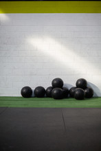 Group Of Black Wall Balls In A Gym Or Fitness Club With White Brick Walls