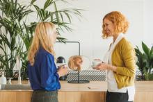 Female Co-Workers Chatting Over Coffee