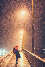 Young Girl With Umbrella Outdoors In Snowfall