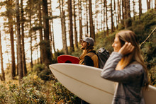 Surf Couple Hiking Through Forest