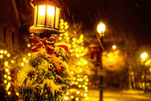 Christmas Tree Branches And A Red Bow On A Lantern Under A Falling Snow. Street Lamp With Christmas Decorations Under The Snow. White Christmas. Blurred Background. Copy Space For Your Text