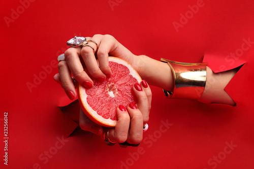 Manicure. Kobiece dłonie z  czerwonymi paznokciami przez otwór w czerwonym tle  trzymają owoc grejpfruta.