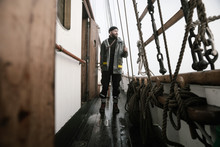 A Man, A Sailor Stands On The Deck Of An Old Sailing Yacht In A Raincoat