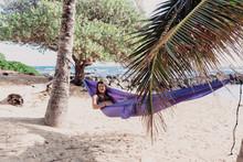 Beautiful Brunette Woman Lying In Hammock On Hawaiian Beach