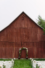 Wedding Arbor In Front Of Rustic Red Barn With Seating For Ceremony