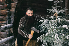 Bearded Man In Norwegian Knitwear Holding Axe And Snow-Covered C