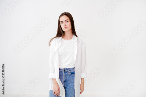 Young pretty woman wearing white shirt against white background