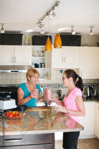 Healthy mature women making morning post-run smoothie together i