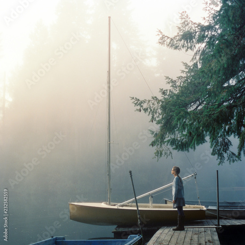 Twelve year old girl stands on a dock on a foggy morning on Fletcher Bay