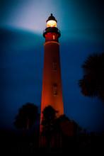 Beautiful Light House At Dusk Shining Bright Into The Night Sky