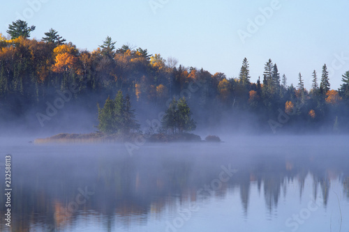 Poster Morning with fog Fog and mist arising from a lake in Quetico Provincial Park, Ontario, Canada in late autumn. Gold leaf trees rimming the shoreline, a small island sitting out in the fog. Photographed on Fuji Velvia film.