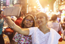 Mother And Daughter Taking Selfie With Smartphone  In A Busy Street At Night