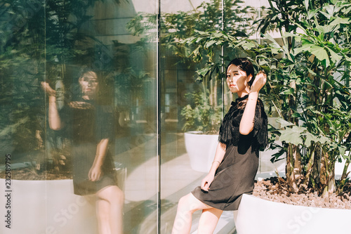 Asian young woman portrait with green plant in sunlight