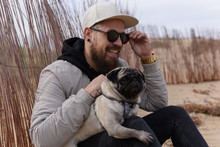 Smiling Man Sitting With Cute Pug