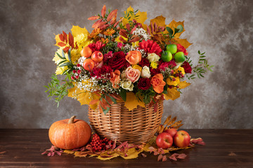 Concept of autumn. Bouquet of beautiful flowers in a basket, pumpkin and yellow leaves