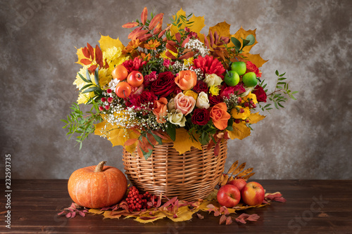 Obraz Concept of autumn. Bouquet of beautiful flowers in a basket, pumpkin and yellow leaves - fototapety do salonu