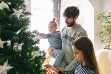Father And Kids Decorating Christmas Tree. Family Celebrating Christmas At Home.