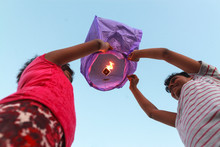 Girls Releasing Sky Lantern To...