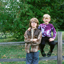 Two Brothers Pose On A Split Rail Fence At On Apple Orchard