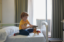 Child Patient Playing With Toy Dinosaur In A Hospital Room