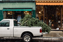 Pickup Truck Hauling A Christmas Tree In A Snowy Village