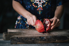 Person Slicing Ripe Red Pomegranate