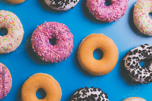 Deurstickers Dessert Top view of many colorful donuts on blue background.