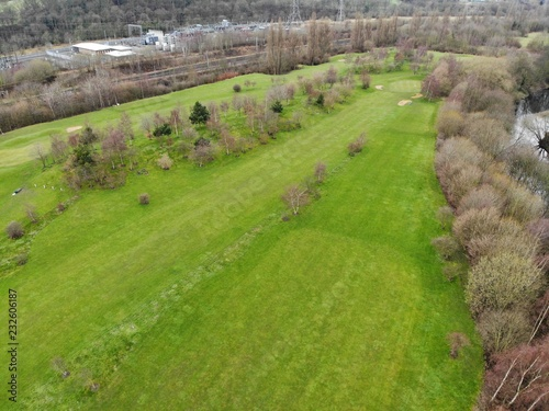 Aerial shot of a Golf course showing houses and trees with green grass.
