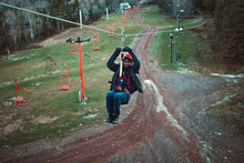 A Young Man Zip Lines Downhill...