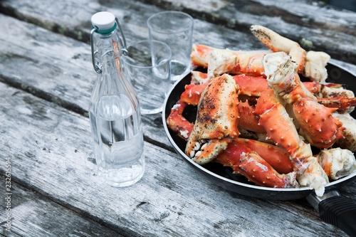In de dag Schaaldieren Gekochte Königskrabben, King Crab und eine Flasche Wodka auf einem Holztisch