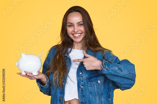 Fototapeta Happy girl showing white piggy bank obraz