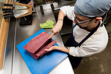 Young Man Slicing Tuna Meat
