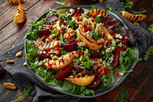 Grilled Quince Salad With Baked And Fresh Grated Beetroot, Blue Cheese, Walnuts On Wooden Rustic Table