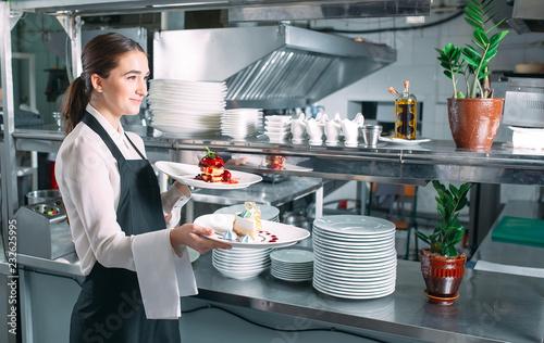 Zdjęcie XXL Kelner służący w ruchu na służbie w restauracji. Kelner nosi naczynia.