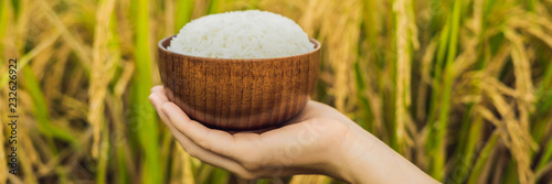 Photo  The hand holds a cup of boiled rice in a wooden cup, against the background of a