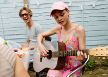 A Woman Playing A Guitar At A Gathering Al Fresco While A Happy, Laughing Man Looks On